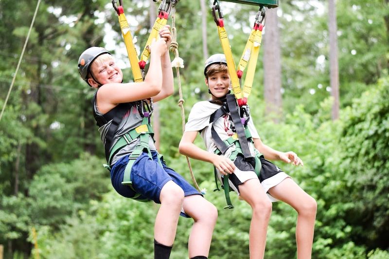 two boys on zipline in forest