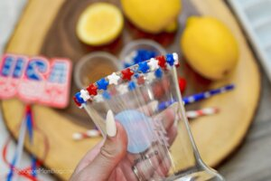 decorating the rim of a hurricane glass with red white and blue star sprinkles