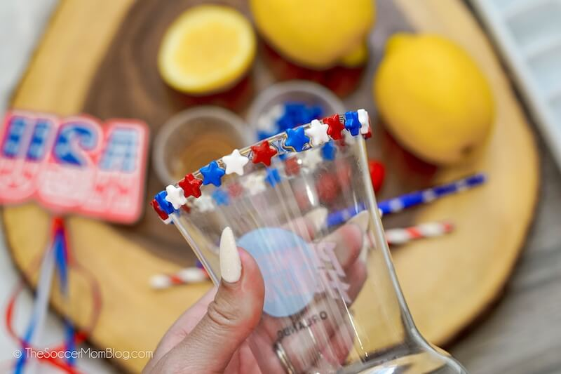 putting red white and blue sprinkles on the rim of a hurricane glass