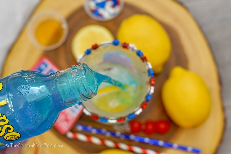 pouring blue lemonade into hurricane glass