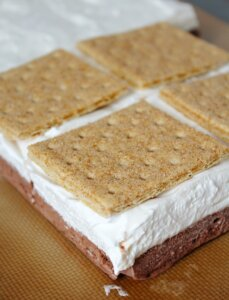 placing graham crackers on top of frozen smores