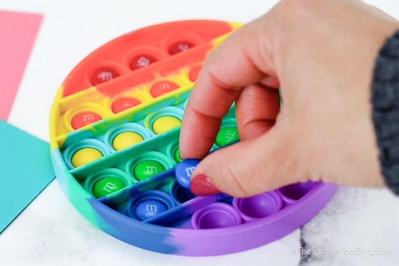 placing M&Ms inside a pop-it fidget toy