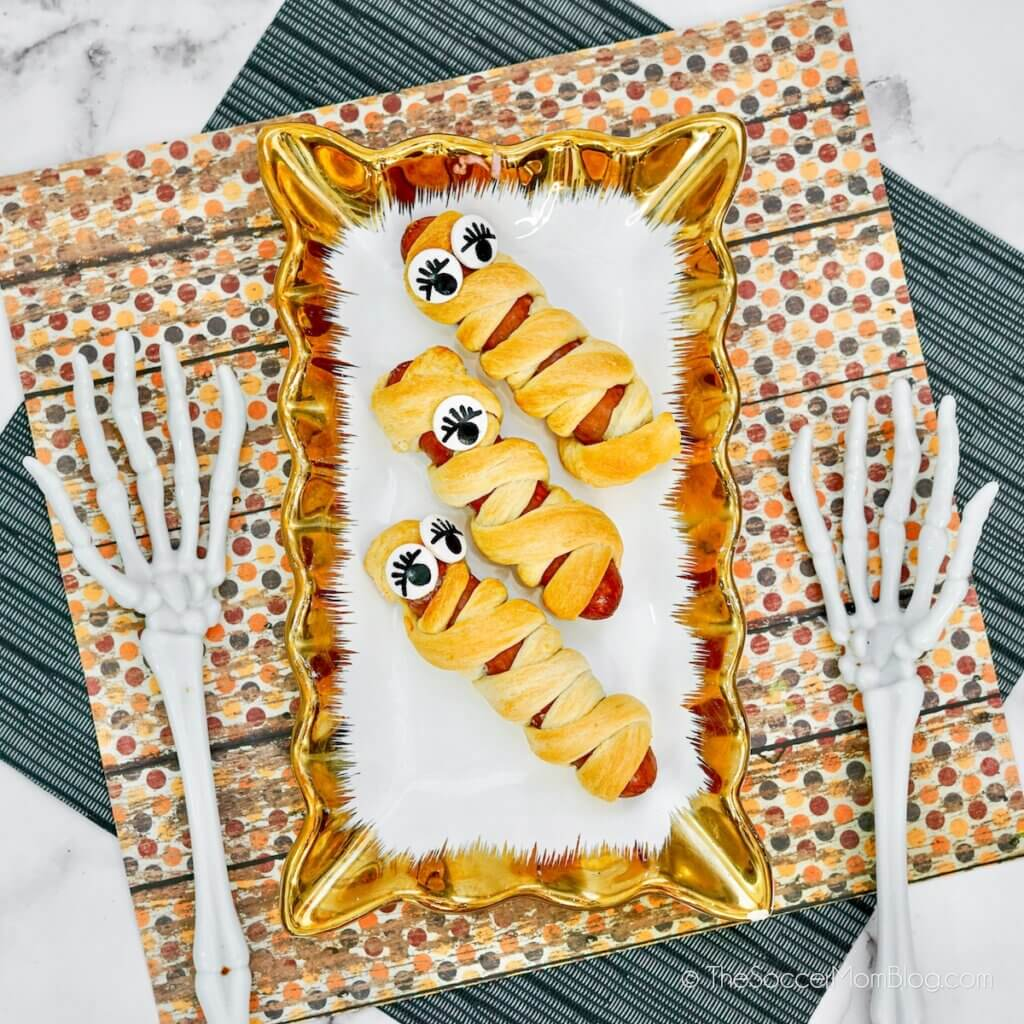 mummy hot dogs on a plate with Halloween decor