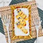Hot Dog Mummies on a plate with Halloween decor