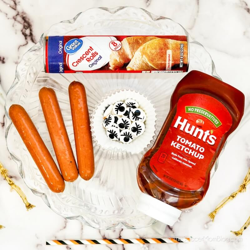 hot dogs, crescent rolls, candy eyeballs, and ketchup bottle on counter