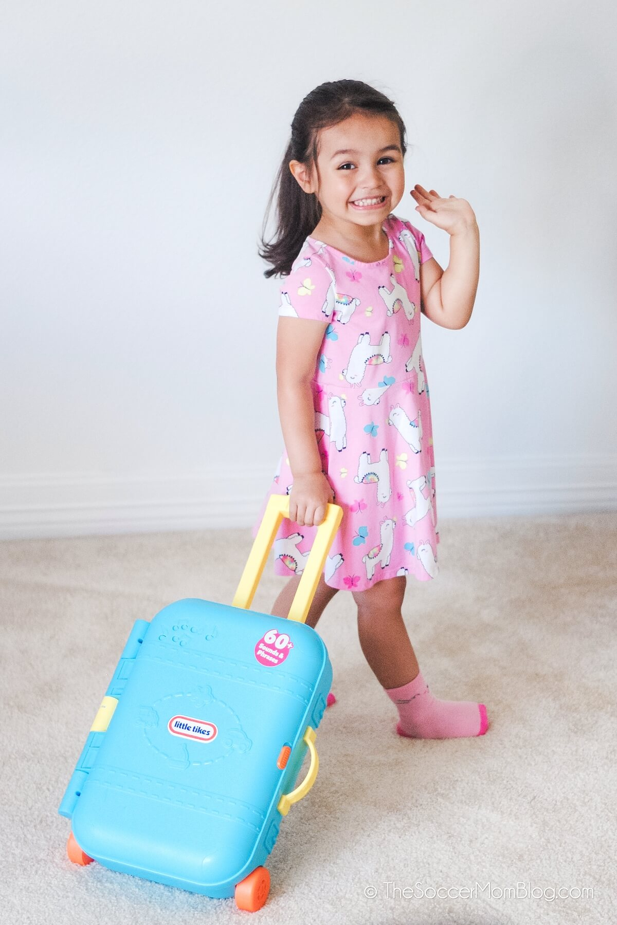 little girl with toy rolling suitcase
