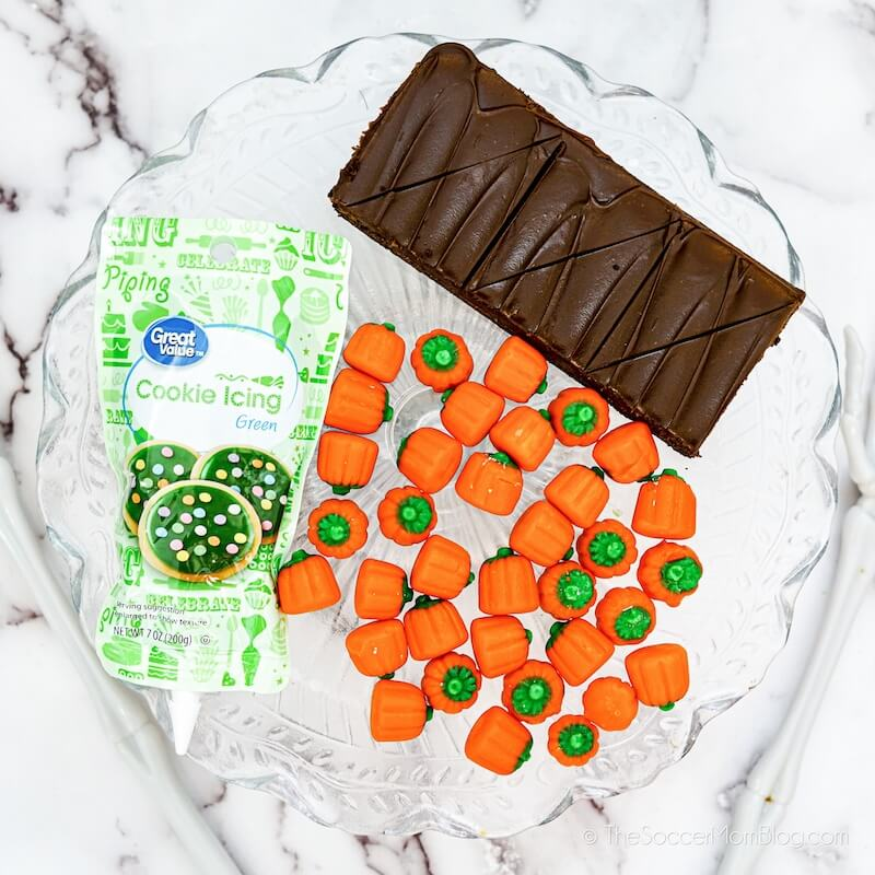 brownies, candy pumpkins, and green cookie icing on counter